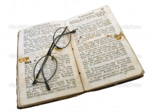 Isolated old open book with glasses against the white background